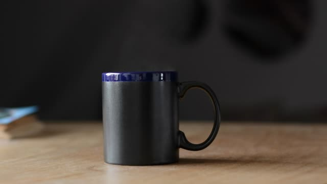 Hot black mug with steam above it video