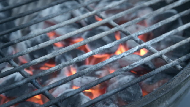 Hot charcoals on an old fashioned backyard Barbecue grill waiting to cook meat for a family dinner