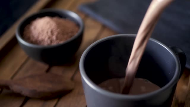 Hot chocolate being poured into a black mug on a dark wood tray. Cocoa powder in the background. Slow motion 50%.