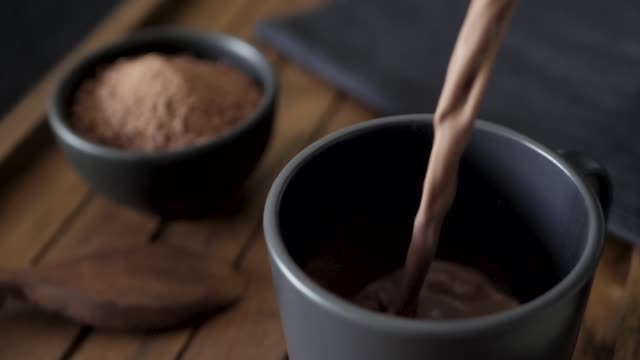 Hot chocolate being poured into a black mug on a dark wood tray. Cocoa powder in the background. Slow motion 25%.