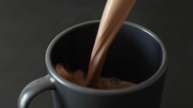 Hot chocolate being poured into a black mug on dark grey background. Slow motion 50%.