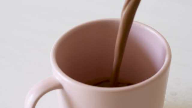 vídeos de stock, filmes e b-roll de chocolate quente que está sendo derramado em uma caneca cor-de-rosa no fundo branco. slow motion 50%. - chocolate quente