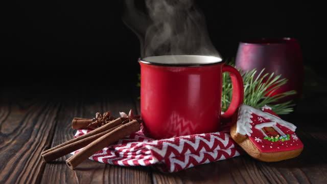 vídeos de stock, filmes e b-roll de chocolate quente na caneca vermelha com canela e gingerbread no fundo de madeira - chocolate quente