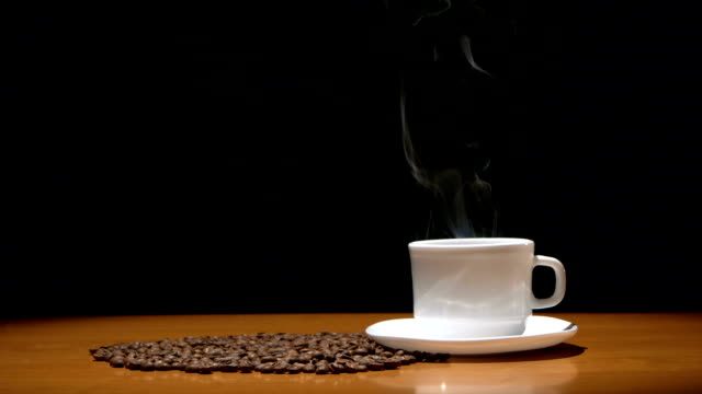 hot coffee cup and beans on wooden table, black background - kaffekopp isolated bildbanksvideor och videomaterial från bakom kulisserna