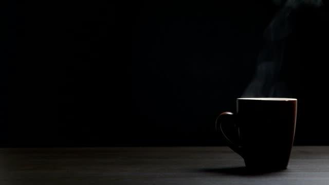 tasse heißen kaffee auf schwarzem hintergrund - kaffeetasse stock-videos und b-roll-filmmaterial