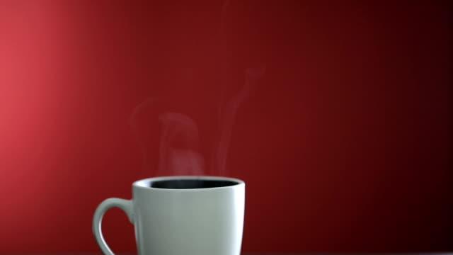 vídeos y material grabado en eventos de stock de hot una taza de café sobre fondo rojo - taza sin platillo
