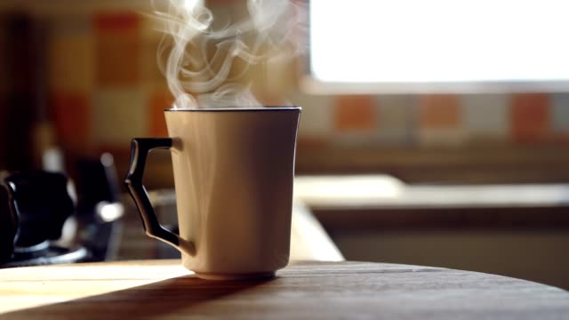 Hot coffee cup steaming on table