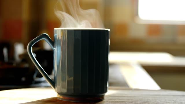 heiße kaffeetasse dampft auf dem tisch - dampfkochen stock-videos und b-roll-filmmaterial