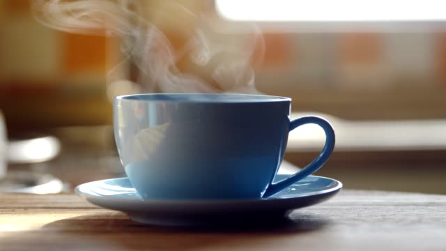 Hot coffee cup steaming on table Hot coffee cup steaming on table coffee stock videos & royalty-free footage