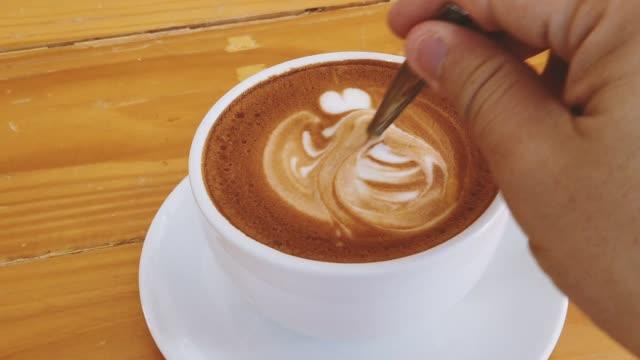 Hot coffee latte art stirring slow motion close-up