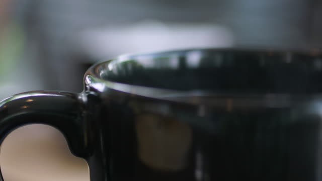 hot coffee steam in black cup - heißes getränk stock-videos und b-roll-filmmaterial