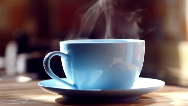 vídeos de stock e filmes b-roll de hot coffee with steam on table - coffee table