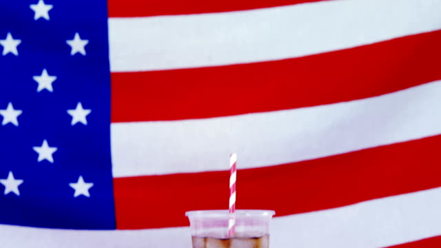 Hot dog and cold drink served against American flag video