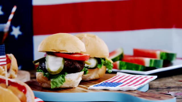 Hot dog and hamburger served on table with 4th july theme video