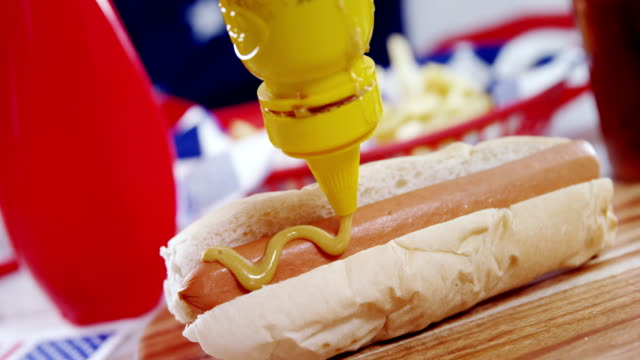 Hot dog with mustard sauce on wooden board video