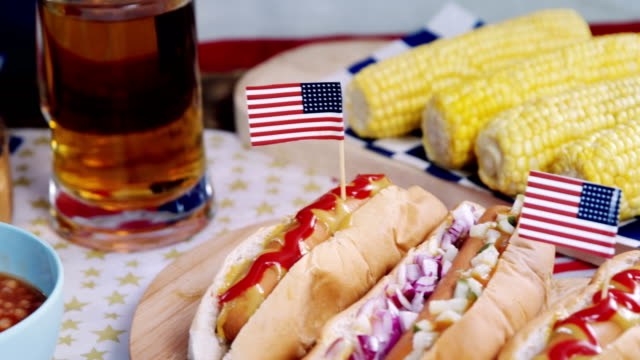 hot dogs on wooden table with 4th july theme - 4 luglio video stock e b–roll
