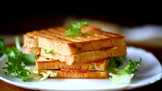 heta dubbel smörgås med sallad lämnar och fyllda i en tallrik - cheese sandwich bildbanksvideor och videomaterial från bakom kulisserna