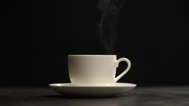 hot drink. steam coming out of cup of tea. black background. 4k - pausa caffè video stock e b–roll