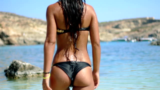 Hot girl enters a transparent sea water on a blue lagoon video