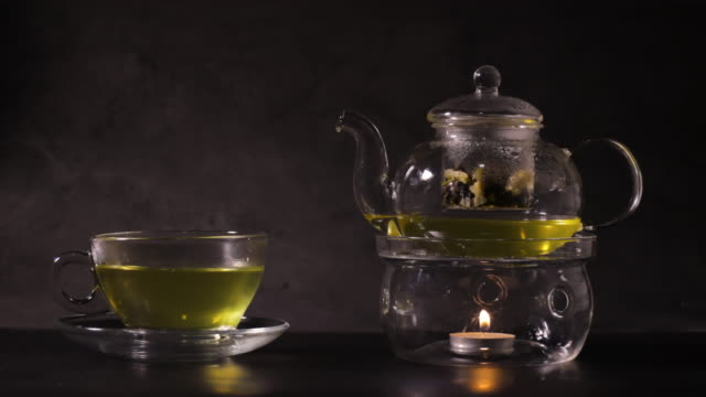 hot green tea in tea cup on kitchen. classic teapot made from glass and boil water by candle. hot drink and tea time concept.