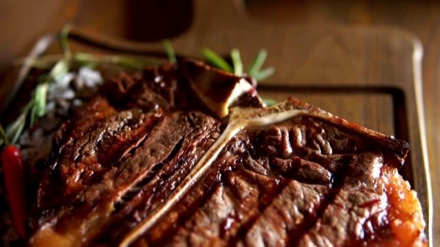 vídeos de stock e filmes b-roll de hot juicy t-bone steak is served at the restaurant on a cutting board - meat plate
