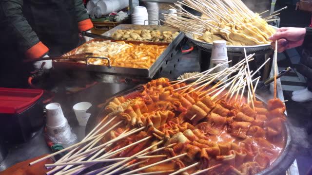 vídeos de stock, filmes e b-roll de vara de oden quente com sopa, rua myeongdong comida, seul, coreia. - coreia