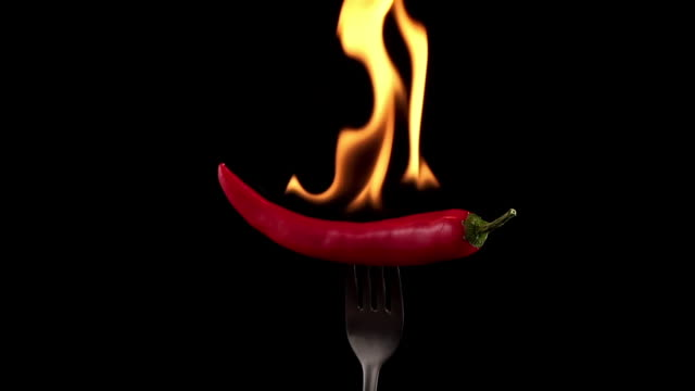 hot red chili pepper on a fork in flames burn - chilli con carne video stock e b–roll