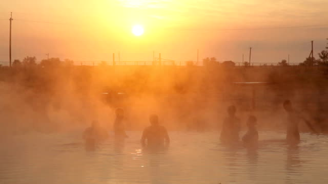 hot spring at sunrise, people swimming video