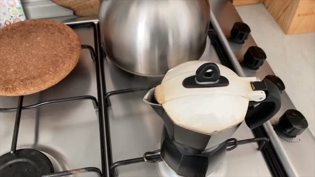 Hot steam comes out of the coffee pot in a domestic kitchen