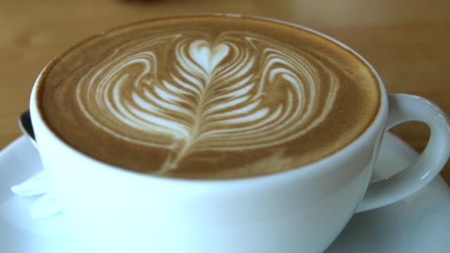 heiße dampfende tasse kaffee stehend auf einem holztisch - cappuccino stock-videos und b-roll-filmmaterial
