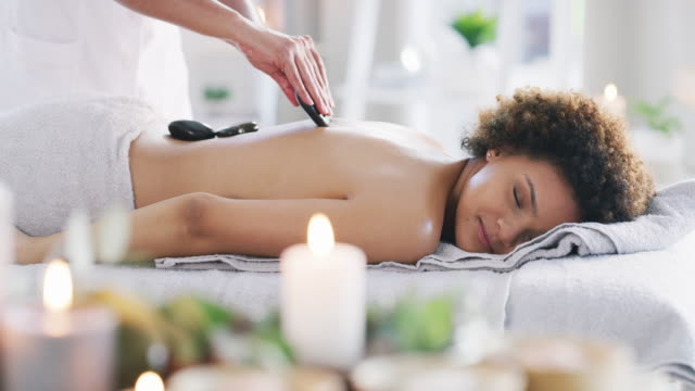 a hot stone massage promotes deep relaxation - attività del fine settimana video stock e b–roll