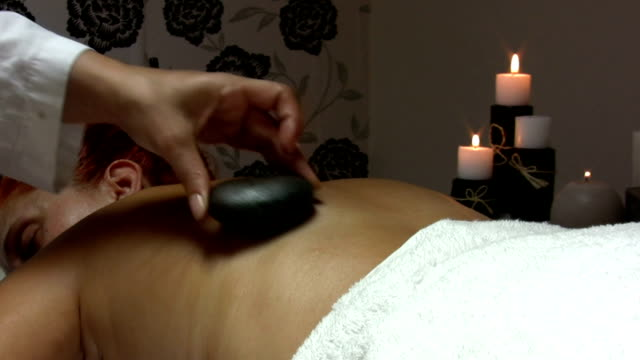 Hot Stone Treatment A woman is getting hot stone massage in day spa. HD 1080i. dyed red hair stock videos & royalty-free footage