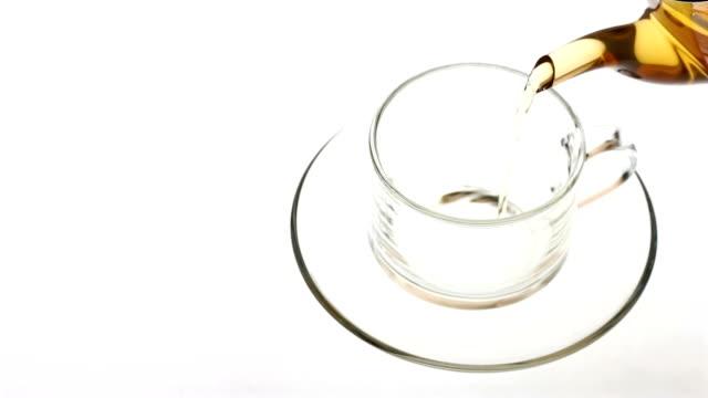 スローモーションでガラスのティーカップに注がれている熱いお茶 - マグカップ点の映像素材/bロール