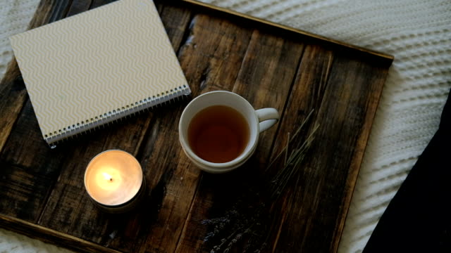 Hot tea, burning candle and notebook on wooden tray in room video