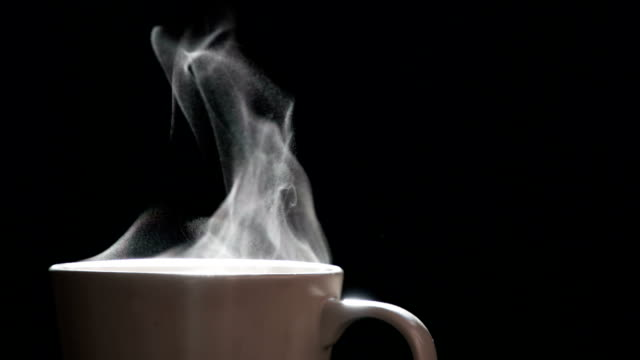 Hot Tea in a Beige Mug A trickle of steam rises and twists gracefully from a cup of hot coffee. Backlight illuminates the beige  of cup  on a black background. Shooting at a rate of 120fps. steam stock videos & royalty-free footage