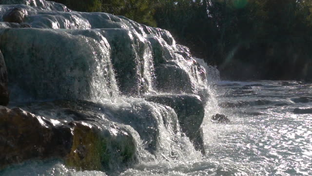 SLOW MOTION: Hot thermal water flowing down rocks splashes and glimmers in sun. SLOW MOTION: Hot thermal water flowing down rocks splashes and glimmers in the bright sunlight. Glassy natural spring water flows from one geothermal pool to another on a sunny day in scenic Tuscany. purified water stock videos & royalty-free footage