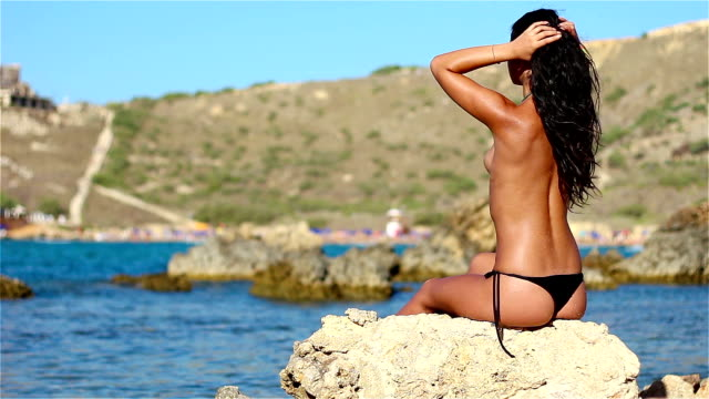 Hot topless girl enjoying on rock by the sea video