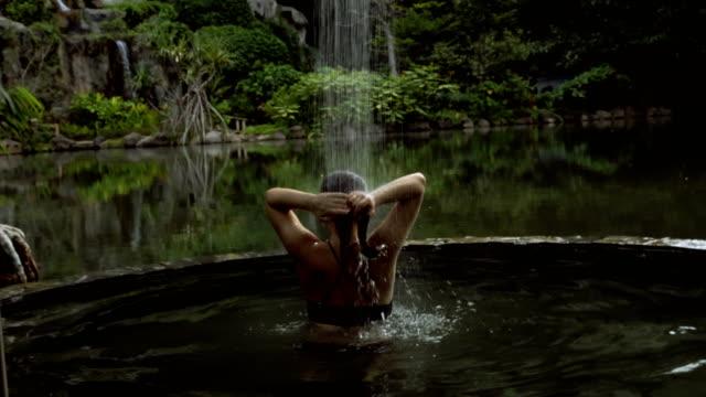 정글에서 뜨거운 욕조입니다. 여자 온천 휴양지에서 휴식 - 스파 온천 스톡 비디오 및 b-롤 화면