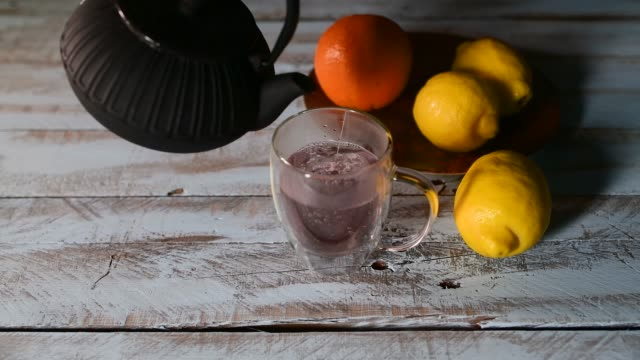Hot water being poured from a teapot into a cup with a tea bag surrounded by lemons and an orange on a wooden table. Relaxation and lifestyle concept.