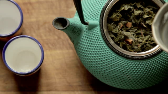 hot water poured inside a tea chest with fresh herb and in the side two ceramic colorful cups hot water poured inside a tea chest with fresh herb and in the side two ceramic colorful cups daylight savings stock videos & royalty-free footage