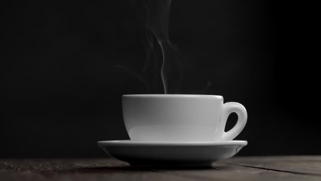Hot white tea or coffee cup on a saucer against black background. Steam or smoke is coming from the cup. Slow motion shot