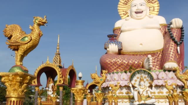 hotei statue outside buddhist temple. traditional happy hotei sculpture located in yard of buddhism shrine against cloudless blue sky in asian country. wat plai laem. koh samui. - buddha video stock e b–roll