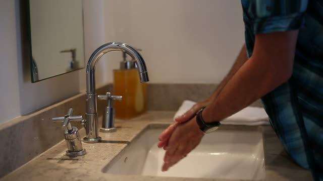 hotel mann hände waschen und wasser zu sparen - wassersparen stock-videos und b-roll-filmmaterial