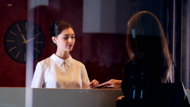 hotel service manager greeting new customer businesswoman. close-up. - hotel checkin video stock e b–roll