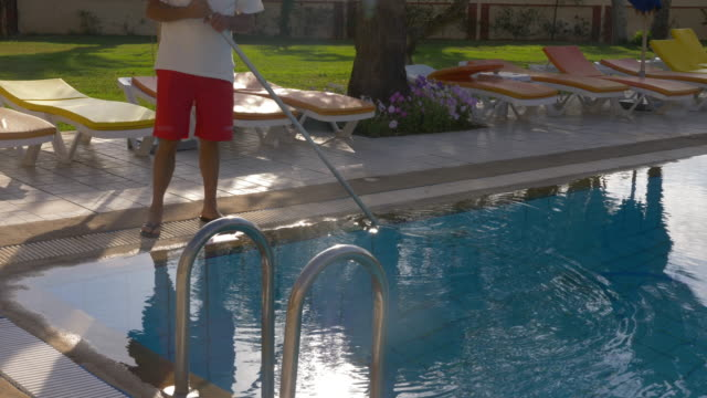 hotel worker cleaning water in swimming pool, cropped view - addetto alle pulizie video stock e b–roll