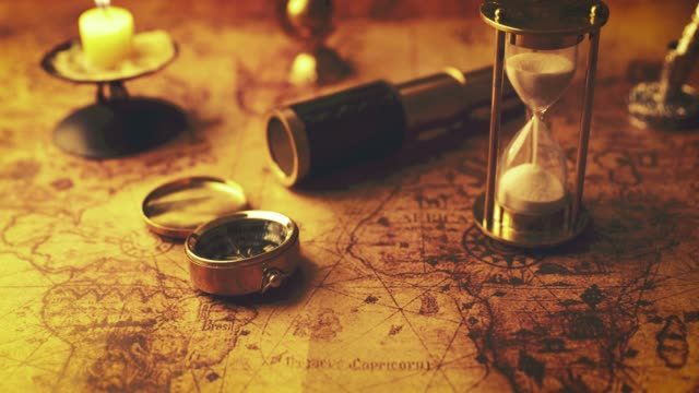 hourglass and ancient navigation items on old world map