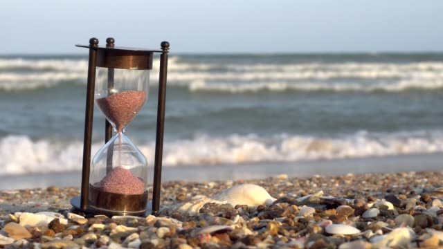 Hourglass on the beach sand beach. Saving time concept