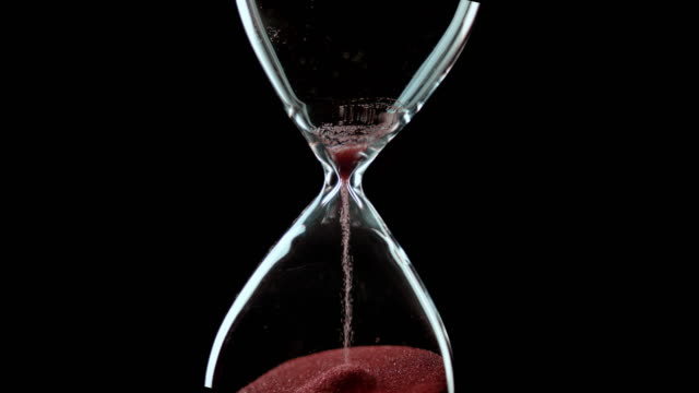 SLO MO LD Hourglass running out of sand against black background