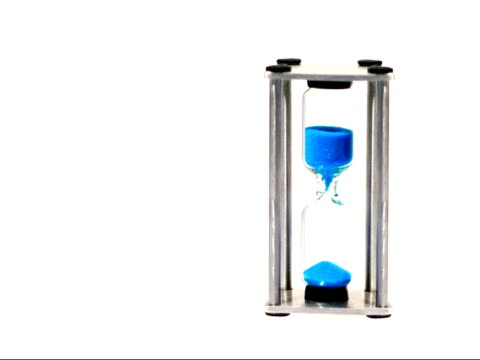 Hourglass Blue sand flowing through an hourglass on a white background. hourglass stock videos & royalty-free footage