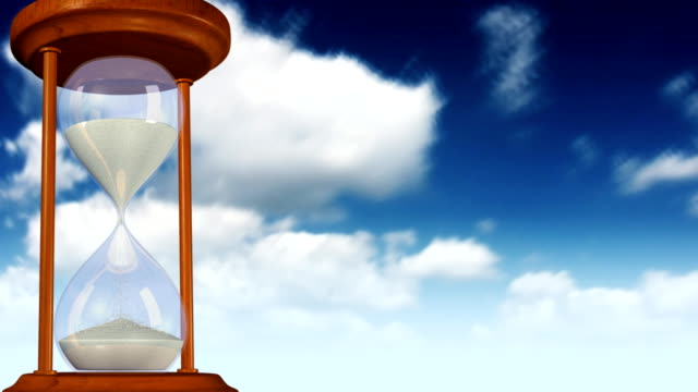 Hourglass with clouds in the background.